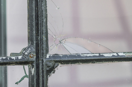 drilled: A hole in the window pane. A broken pane of glass - by bullet drilled through