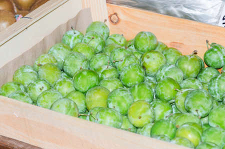 shop for animals: Fresh green fruits on a market in a wooden box.