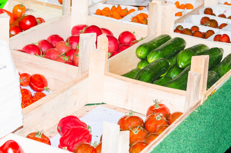 merchandiser: Stand with tomatoes, peppers and fresh green cucumbers on a market.