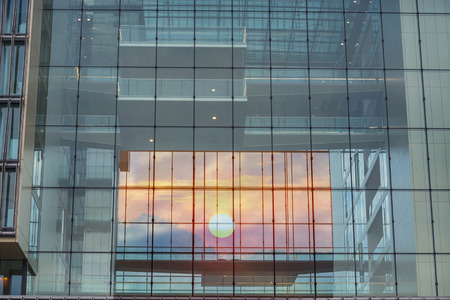 Modern blue glass wall of an office building in the background a sunset. Stock Photo