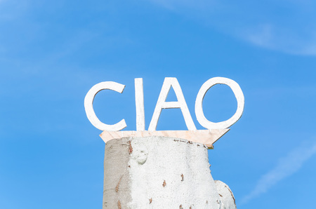 ciao: Ciao lettering on an old tree trunk in front of blue sky.