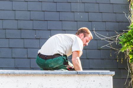 tar paper: Construction worker on the roof of a garage to fix the damage of a tornado.