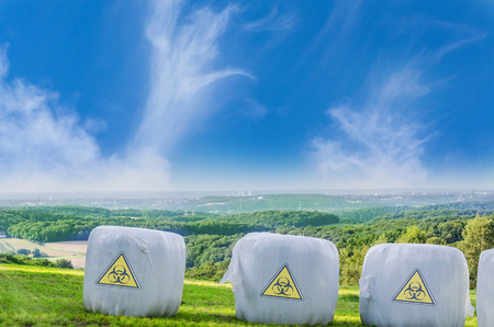 genetically modified crops: Three straw bales with a warning genetic engineering.Photo montage Stock Photo