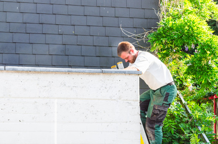 flat roof: Construction worker on a ladder that is leaning against a flat roof.