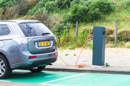 Den Haag, Scheveningen, Pays-Bas - le 17 Juin, 2015: voiture électrique à une station de charge sur le parking de la plage de Scheveningen parking Holland.Seperate avec station de recharge pour les véhicules électriques. Les véhicules peuvent être reliés par un câble à la station pour re Éditoriale