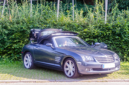 automatic machine: Heiligenhaus, NRW, Germany - July 31, 2014: A male driver in a Chrysler Crossfire Roadster Convertible in automatic machine gray, open the soft top for a ride in good weather. The Chrysler Crossfire is a heckantriebenes vehicle. The Crossfire Wurd, produc