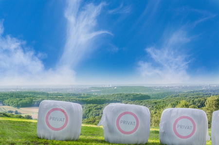 plastic straw: Three straw bales in white plastic film on a field with the Icon Private