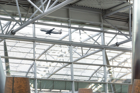 architectural feature: Airport glass roof with steel structure in the background is a take-off Passenger airplane Stock Photo