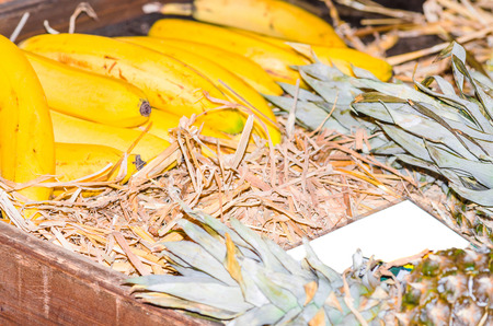 Fresh bananas, pineapple on straw beds for sale at a farmers market.
