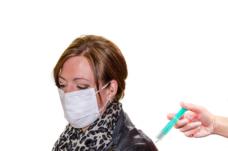 swine flu vaccination: Dark-haired young woman with face mask. At the bottom right of the screen a hand with syringe. Stock Photo