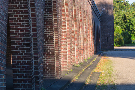 architectural feature: Old building with brick arches along a road. Stock Photo