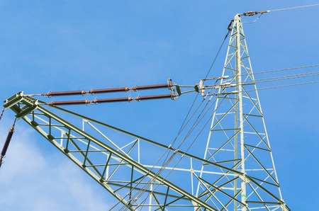 High voltage towers with blue sky in the background.
