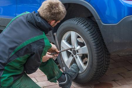 若い男が車のタイヤを交換します。彼の車の冬タイヤを夏タイヤ。