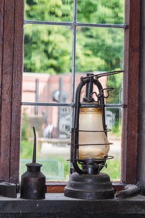 lighting fixtures: Old kerosene lamp on a window sill in the background a lattice window.