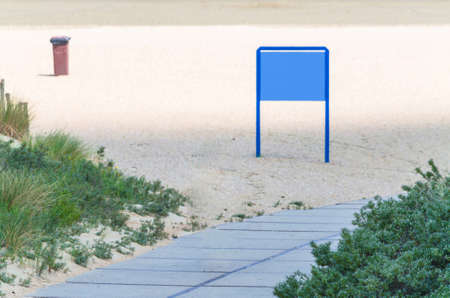 the silence of the world: Way to the beach overlooking a blue sign. Stock Photo