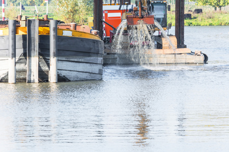 dredging: Dredging in the harbor basin for a deeper harbor. Stock Photo