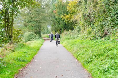 dysentery: Essen, Germany - September 30, 2014: group of older men cycling on the promenade of the river Ruhr near Essen Werden towards Kettwig.