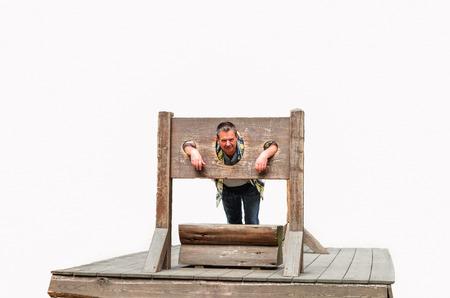 Man gevangen in een middeleeuws martelwerktuig. Pranger tegen een witte achtergrond. Stockfoto