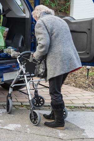 mujeres maduras: se�ora mayor que se coloca con un andador en el coche. Foto de archivo