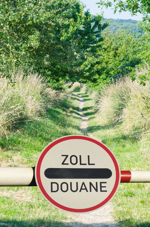 prohibitions: Tollgate with demarcation and road sign customs office between two countries.