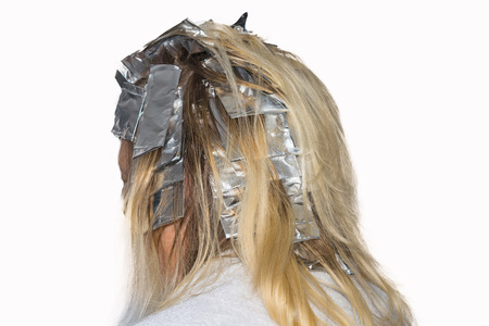 blond streaks: Woman with blond hair in preparation for hair dyeing. Hair highlights wrapped in aluminum foil.