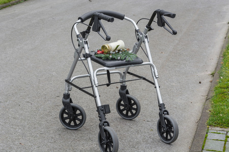 transience: Rollator walker with grave candle, symbol of grief and transience.