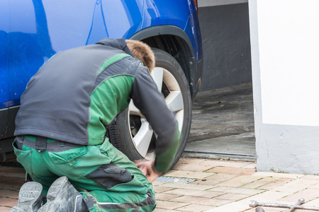 winter tires: Young man  exchanging the car tires. From summer tires on winter tires on his car.