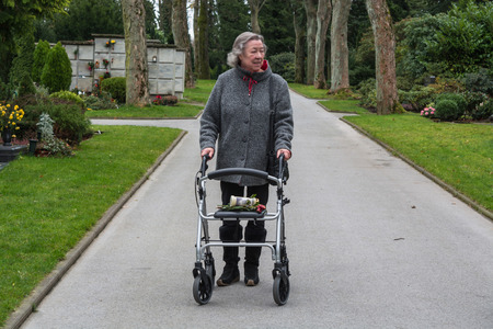 great grandmother: Elderly lady with a walker on a walk in a cemetery.