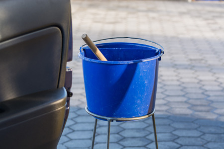 the car window: Blue bucket with water at a gas station to clean the windshield.