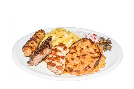 carnes y verduras: Típico plato de barbacoa griega con diversas carnes, ensalada y papas fritas. Foto de archivo