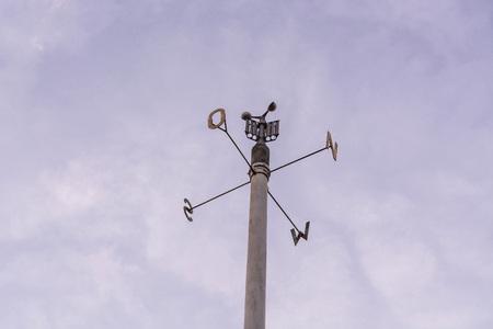 Estación meteorológica con anemómetro en el cielo azul.