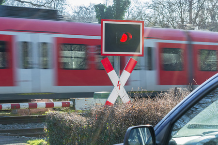 railroad crossing: Waiting at a railroad crossing while a fast passenger train drives past. Intentional motion blur.