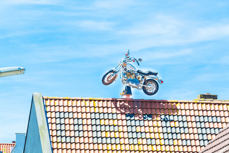 harley davidson motorcycle: Ouddorp, Zeeland, The Netherlands - June 15, 2015: Strange old Harley Davidson motorcycle on the roof of a house for advertising purposes.