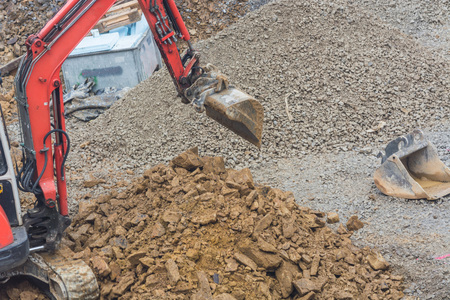 dredging tools: Mini excavator with excavation work for a new construction home. Stock Photo