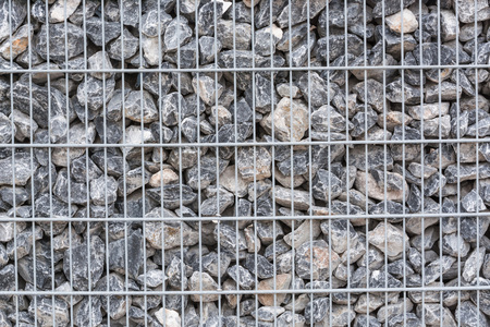 gratings: Gabion filled with thick stones; Metal Stone basket with large natural stones for external landscaping. Stock Photo