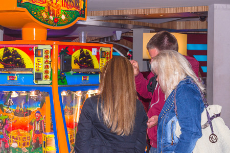 three persons: RENESSE, ZEELAND, THE NETHERLANDS - JUNE 14 2015: Three persons standing on a slot machine in a casino a casino.Visiting in the Dutch seaside resort of Renesse on the Iceland of Schouwen-Duiveland in the province of Zeeland Netherlands.