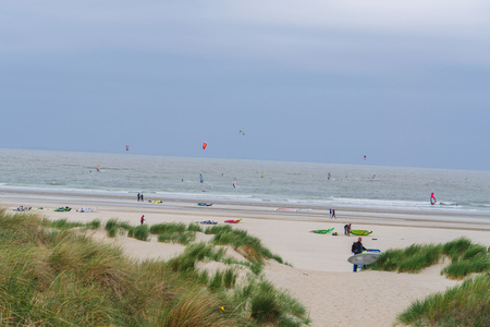 windsurfers: Brouwersdam, ZEELAND, NETHERLANDS - JUNE 13, 2015: Brouwersdam, North Sea kitesurfers, windsurfers in stormy seas on the beach. Strong wind by sand drifts and poor visibility.