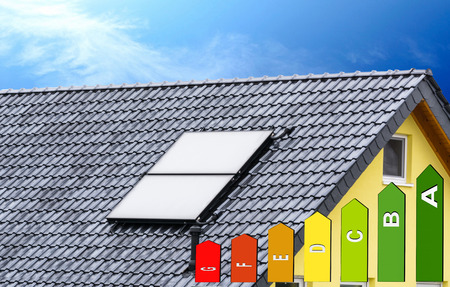alternative energy sources: Solar panels on the roof of a house with blue sky in the background and energy labeling.