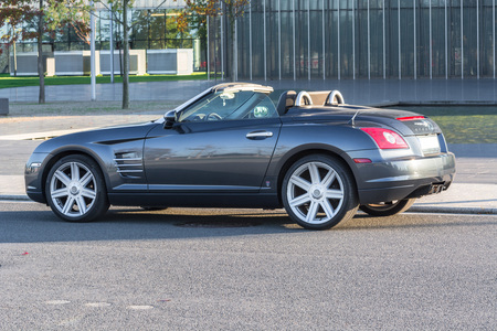 sideview: EAT, NRW, GERMANY - OCTOBER 11, 2015: Chrysler Crossfire, sideview of the new administrative building of ThyssenKrupp in Essen, Germany.