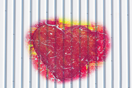 Silver colored textured metal wall with painted red heart.