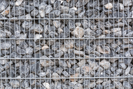 gabion mesh: Gabion filled with thick stones; Metal Stone basket with large natural stones for external landscaping. Stock Photo