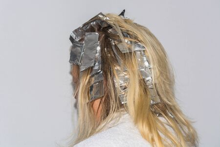 aluminum foil: Woman with blond hair in preparation for hair dyeing. Hair highlights wrapped in aluminum foil.