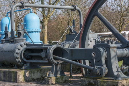 water turbine: Old industrial sewing machine, water turbine on a concrete base. Stock Photo