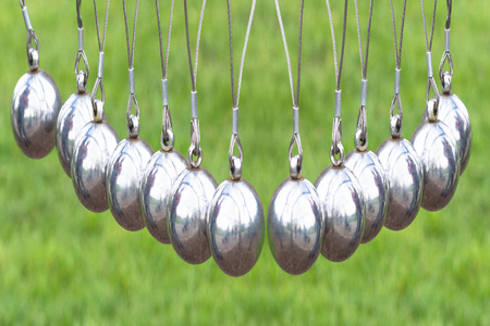So Newtons Cradle or pendulum ball, Newton pendulum called Newtons cradle.Physics is action, reaction and concept or cause and effect. Stock Photo