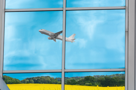 Beautiful glass building facade with reflections of an airplane during startup.