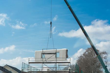 Een muur deel van een geprefabriceerd huis op een kraan tegen de blauwe hemel.