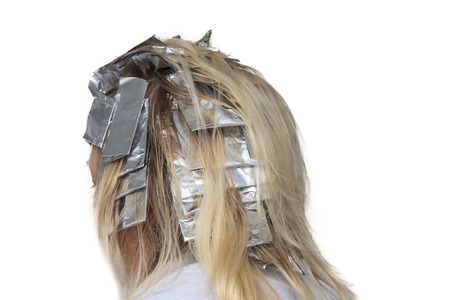barber: Woman with blond hair in preparation for hair dyeing. Hair highlights wrapped in aluminum foil.