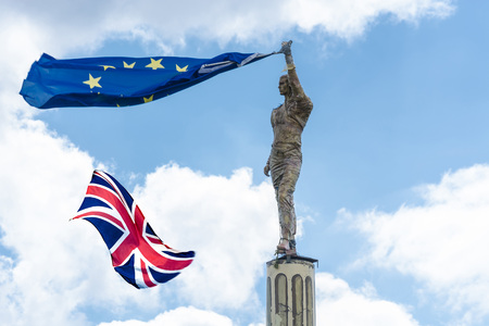 Proposed referendum on United Kingdom membership of the European Union, antique stone statue holds a European flag in hand including the British Flag. Stock Photo