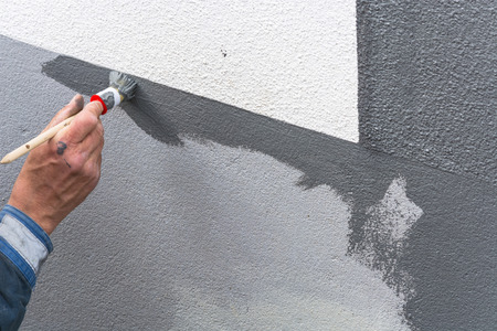 housebuilding: Close-up, arm of a house painter with paint roller in hand painting a house wall with gray paint.