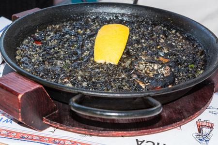 marisco: Arroz Negro black paella with seafood in a Paellera. Stock Photo